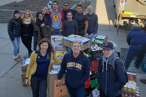 Volunteers load a truck with canned foods for delivery to the Downtown Mission.