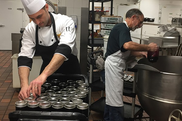 Paolo Vasapolli packs jars of jam being filled by Steve Daigle.