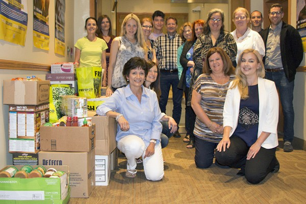 staff posing alongside boxes of canned foods