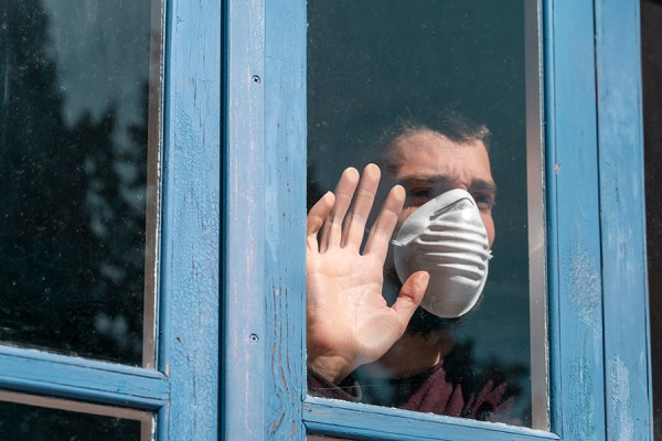 Man wearing face mask looking out window