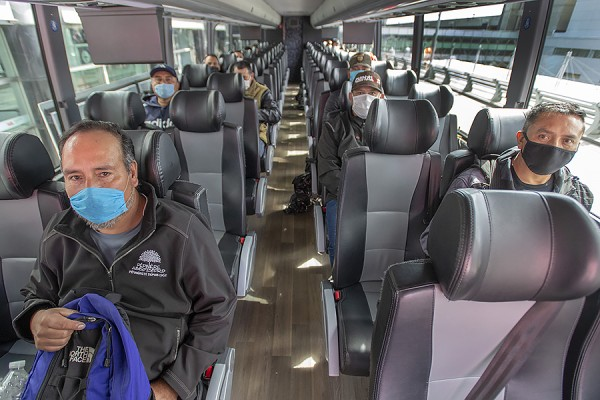 Migrant workers wearing face masks on a bus