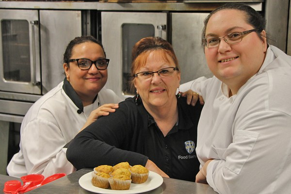 Food Services staff pose with muffins