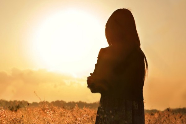 woman silhouetted against sun