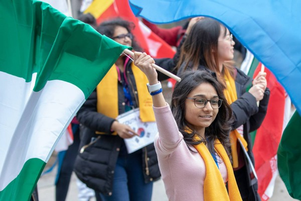 International students carrying flags of many countries