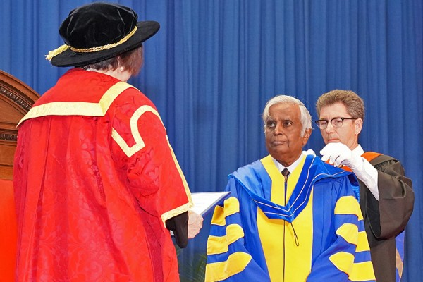 Datta Pillay receives the hood of his honorary doctorate during 2019 Spring Convocation ceremonies.