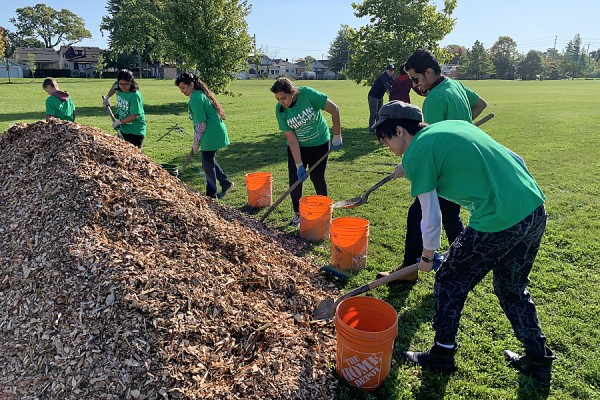 Students shovel mulch to place around newly-planted trees in Gignac Park.