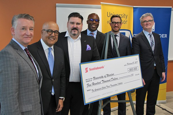 Douglas Kneale, Alex Besharat, Terry Roman, Charles Achampong, Sean White, Bill Anderson posing with large comically cheque