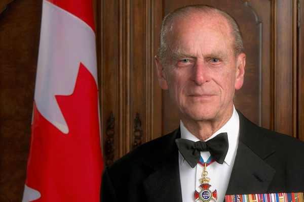 Prince Philip posing before Canadian flag