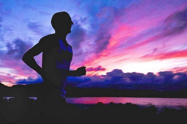 runner silhouetted against sky