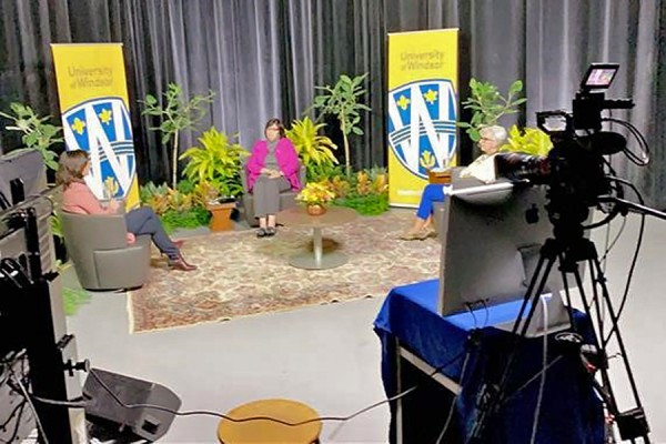Video cameras frame a panel discussion.