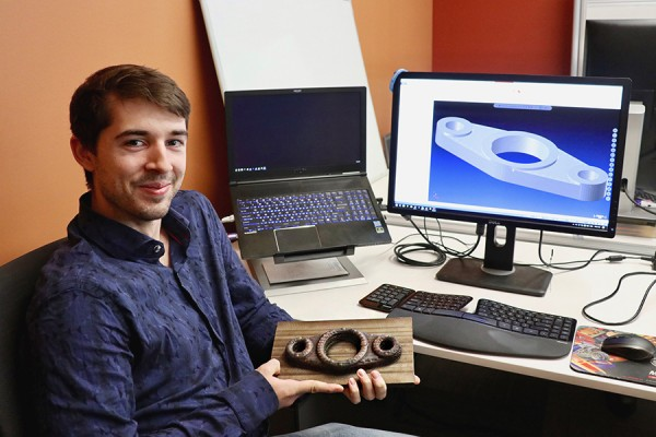 Shane Peelar, a doctoral student of computer science, displays a sample machine part created by three-dimensional printing.