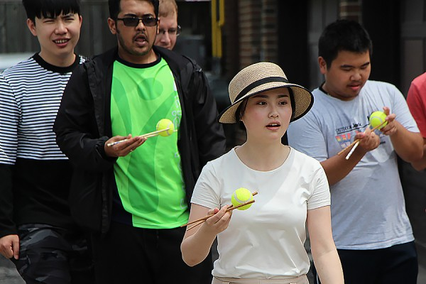 Stella Jiang holds a ball with chopsticks in the first leg of the Trivia Tower Race, one of the activities held Friday for World Student Day.