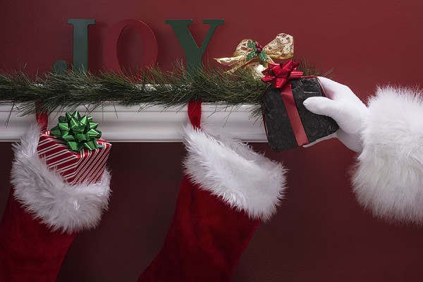 Hand placing gift in stocking hung on fireplace