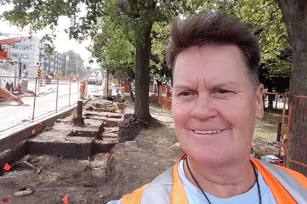 Terri Fletcher standing in front of dig site along Sandwich Street.