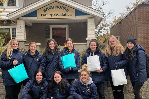 Members of the Lancer women's hockey team hold bags of donated goods