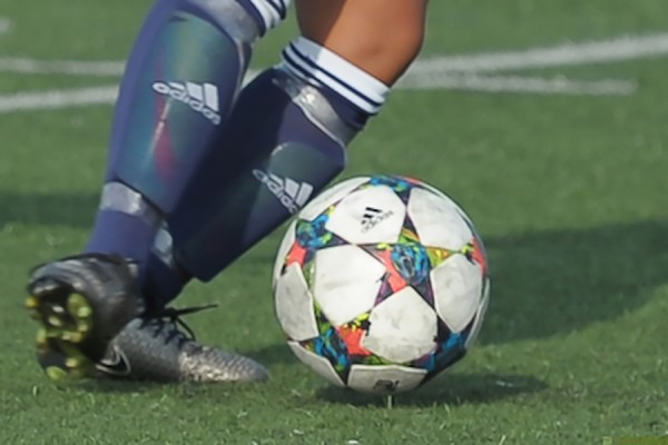 feet in cleats chasing soccer ball