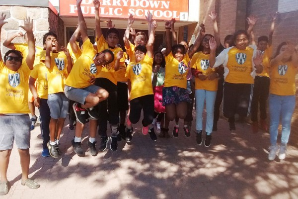 Students at Derrydown Public School inToronto jump in the air while wearing yellow University of Windsor t-shirts.