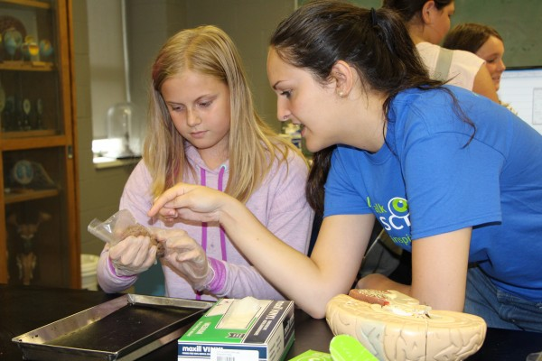 Let's Talk Science volunteer Nina Milidrag (l.) helped the sixth grader Morgan Curtis (r.) examine a sheep's brain during St. Anthony Catholic School's field visit to UWindsor, June 17.