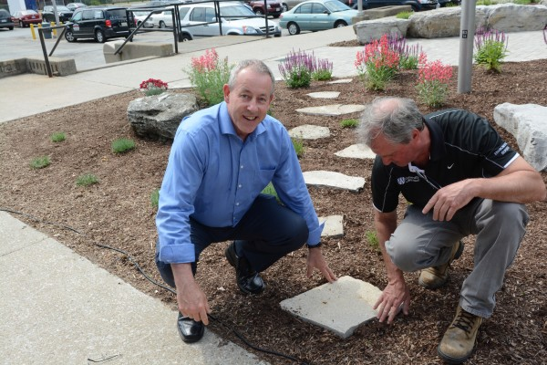 Athletic director Mike Havey placed a paving stone representing his department's 100 percent participation in the perennial garden outside the Leddy Library during a donors appreciation reception, Thursday.