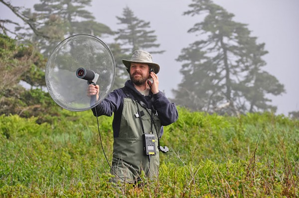 UWindsor biology associate professor Dan Mennill records the acoustic communication of a Savannah Sparrow on Kent Island.