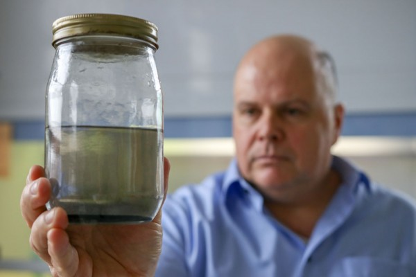 UWindsor's Joel Gagnon, associate professor and department head of Earth and Environmental Sciences, examines a sample of well water taken from a residence in Chatham-Kent.