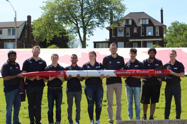 University of Windsor mechanical engineering students pose with the rocket they entered in The Spaceport America Cup. The team placed fifth in the 30,000 commercial off the shelf motor, solid propulsion category.