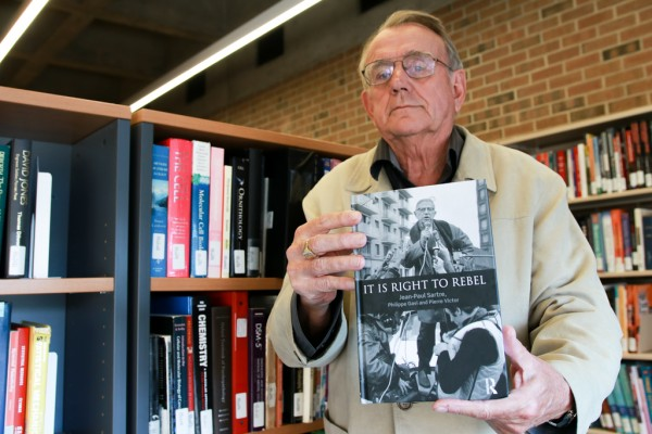 Professor emeritus Adrian van den Hoven displays It Is Right To Rebel by Jean-Paul Sartre, Philippe Gavi and Pierre Victor. Van den Hoven and professor emeritus Basil Kingstone translated the book from its original French to English.