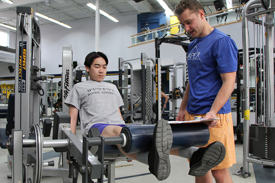 Fit Together participant Nicolas Tran builds up his leg strength under the watchful eye of volunteer trainer Tyler Snyder.