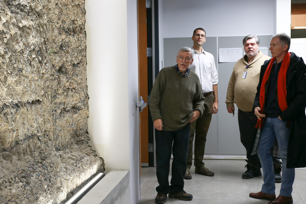 Richard Householder, Trevor Pittman, Bruce Kotowich and Alan Wildeman examine the Armouries original foundation which remains on display in the new building.