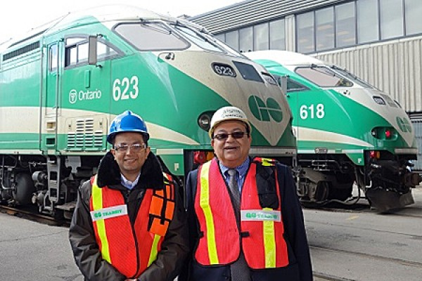Ahmed Fayek and UWindsor engineering professor Waguih ElMaraghy pose in front of GO trains.