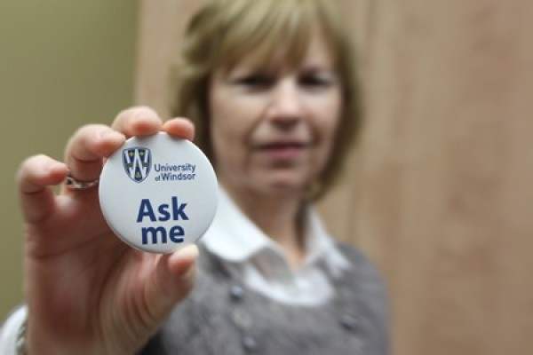 Joanne Gibbs exhibits a button inviting questions from newcomers to campus.
