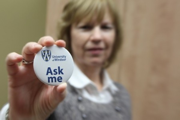 "woman holding ""Ask Me"" button"