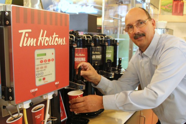 Mark Bagley, manager of satellite operations, tests new Tim Hortons self-serve coffee carafes after their installation Friday in the Marketplace.