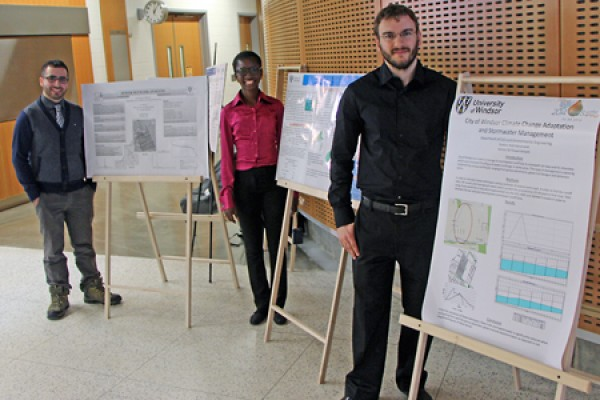 Aojeen Issac, Omotola Ajao, and Rafal Marynowski next to poster boards