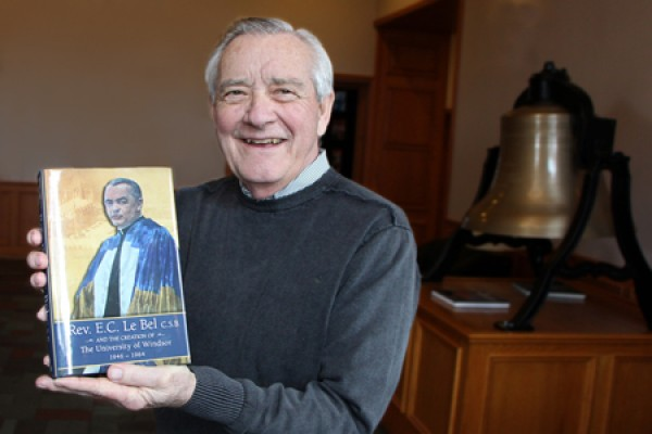 Historian George McMahon poses with a copy of his latest book in the lobby of Assumption University.