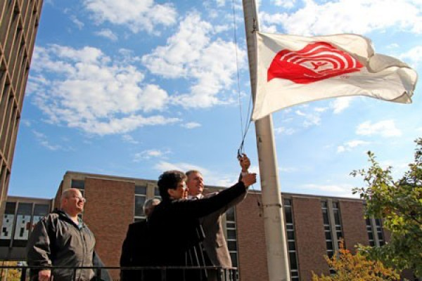 Members of the United Way campaign team raise the charity's flag outside Chrysler Hall Tower