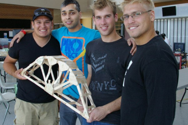 Students pose with their popsicle stick bridge