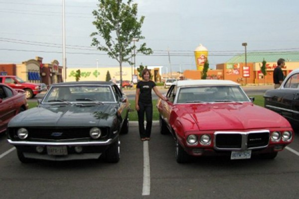 Woman poses between two 1969 muscle cars.