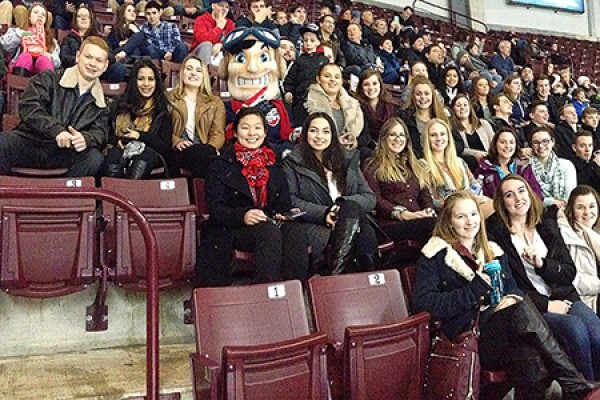 Sport management students surround Windsor Spitfires mascot Bomber during a game at the WFCU Centre.