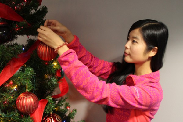 Jeslyn Xie adds a glass ornament to the Christmas tree in the International Student Centre lounge.