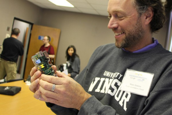 Marc Dubois, a teacher at Ecole secondaire L'Essor, looks over a Raspberry Pi.