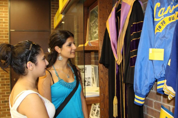 A graduation gown and a varsity jacket are among the artifacts viewed by first-year students Shahad Bahi and Mariam Shamoun.