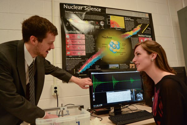 Andrew Ouellette demonstrates an experiment to Physics Club president Melissa Mather