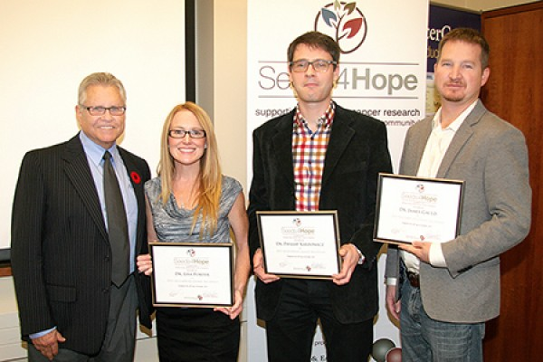 Seeds4Hope administrator Michael Dufresne congratulates research grant recipients Lisa Porter, Phillip Karpowicz and James Gauld.
