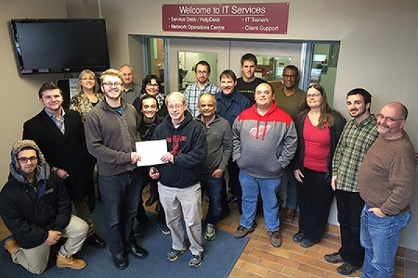 IT Services staff surround Club SODA president Billy Chandler as he presents a certificate of appreciation for the department's work to Andy Kozak.