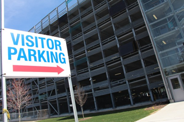 """Visitor Parking"" sign in front of garage"