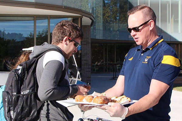 student accepting fritter from Chris Busch