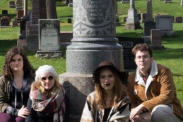 Members of the cast of Queen Milli of Galt pose below the grave marker of Millicent Milroy