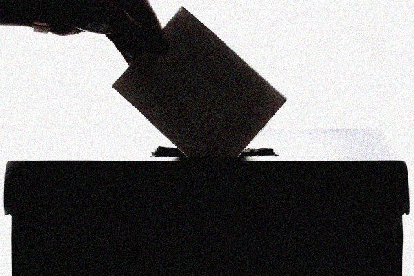 hand placing ballot in box