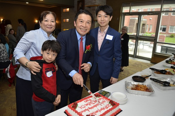 Ben Kuo cuts into a cake with his wife and two sons